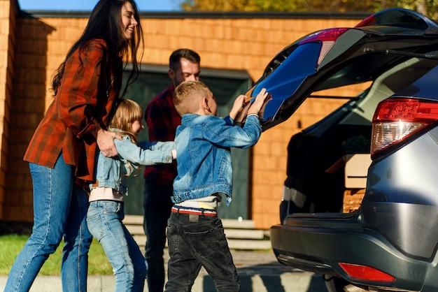 Szczęśliwa rodzina ładuje bagaż do bagażnika samochodu, jadąc na rodzinne wakacje.