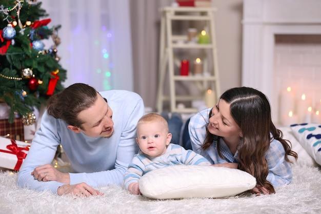 Szczęśliwa rodzina leżąca na podłodze w udekorowanym świątecznym pokoju