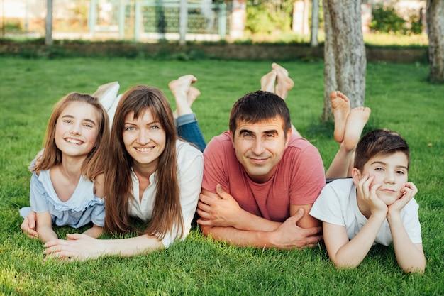 Szczęśliwa rodzina leży na zielonej trawie i patrząc na kamery