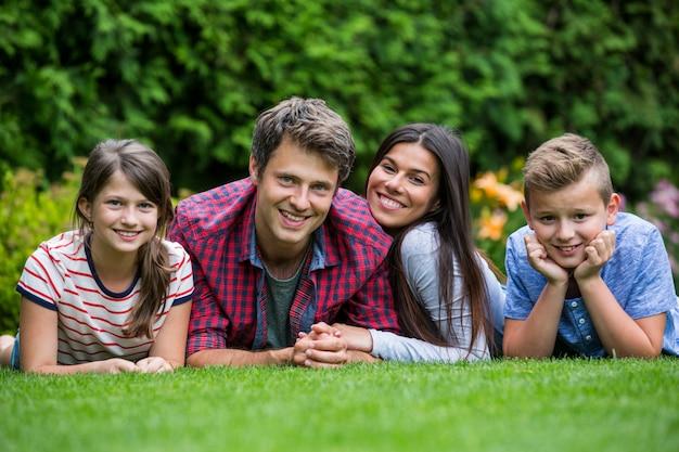 Szczęśliwa rodzina leży w parku