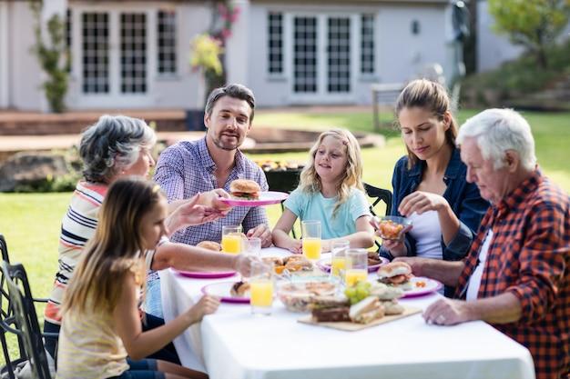 Szczęśliwa rodzina ma lunch w ogródzie