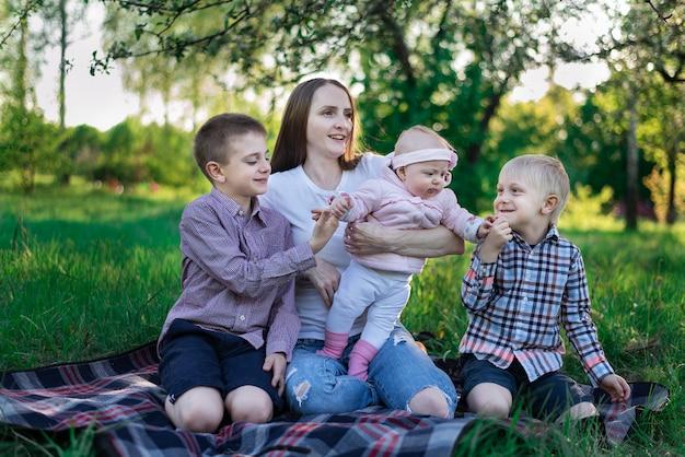 Szczęśliwa rodzina ma piknik w naturze. matka z trójką dzieci. pojęcie macierzyństwa rodzicielstwa