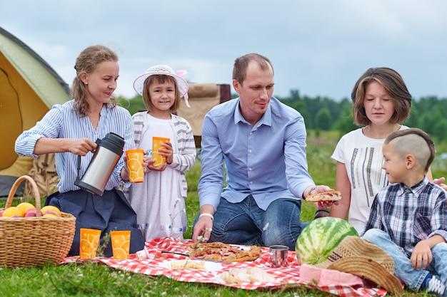 Szczęśliwa rodzina ma pinkin w łące na słonecznym dniu. rodzina spożywająca wakacje na kempingu na wsi