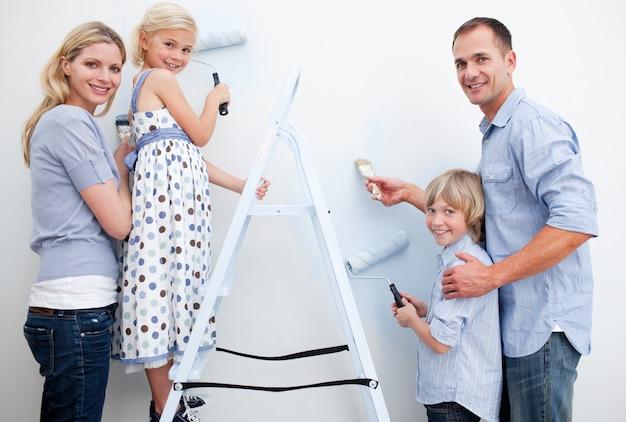 Szczęśliwa rodzina maluje pokój ze szczotkami