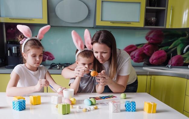Szczęśliwa rodzina: mama, córka i syn z uszami królika przygotowują się do wakacji, kolorując jajka w przytulnej kuchni domu. przygotowania do świąt wielkanocnych