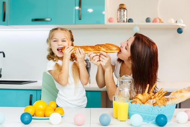 Szczęśliwa rodzina, mama i córka jedzą jeden chleb gryzący z różnych stron. relacje rodzinne dziecka z rodzicami