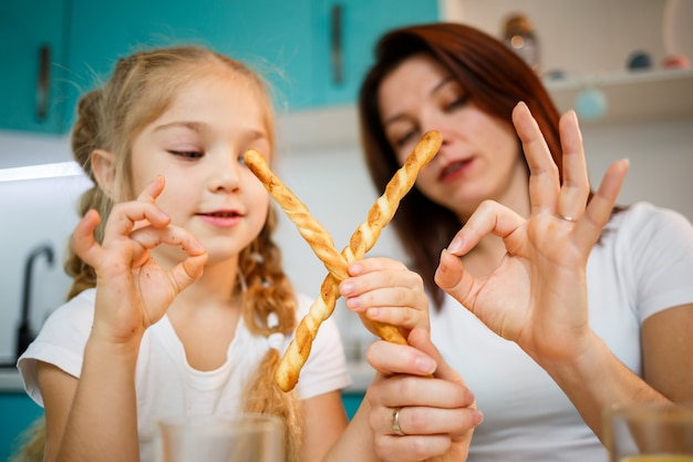 Szczęśliwa rodzina, mama i córka siedzą w kuchni i jedzą paluszki chlebowe. relacje rodzinne dziecka z rodzicami