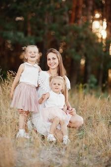 Szczęśliwa rodzina, mama i dwie córki. matka bawi się z córką na ulicy o zachodzie słońca. koncepcja rodziny