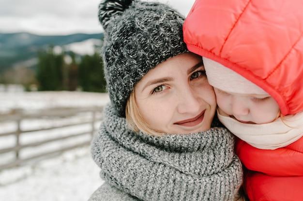 Szczęśliwa rodzina mama przytula dziewczynę i zabawy w śnieżną zimę, spacer w górach, natura. matka i córka cieszą się podróżą.