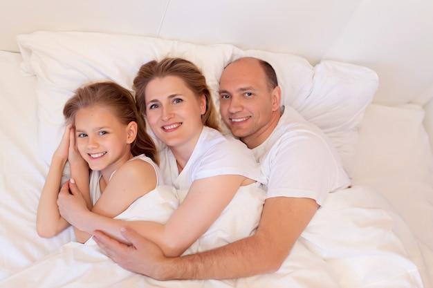 Szczęśliwa rodzina, mama, tata, córka śpią w łóżku w sypialni w domu