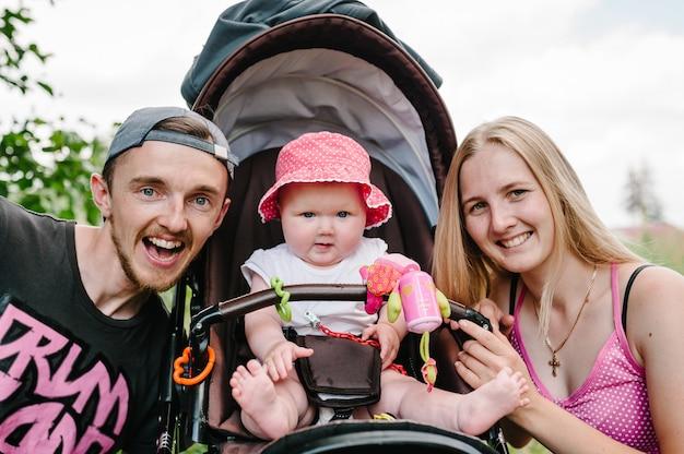 Szczęśliwa rodzina: mama, tata i córka na zewnątrz. matka, ojciec i dziewczyna.