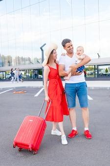 Szczęśliwa rodzina mama, tata i dziecko na lotnisku z czerwoną walizką jedzie w podróż lub wakacje