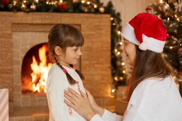 Szczęśliwa rodzina matka i córeczka bawią się w wigilię bożego narodzenia, pozują przy kominku, mama mówi swojej córeczce coś ciekawego