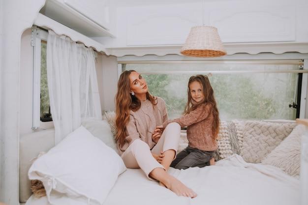 Szczęśliwa rodzina - matka i córeczka relaks na wsi wewnątrz białego skandynawskiego rustykalnego wnętrza kampera.