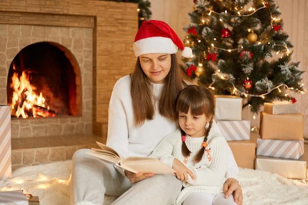 Szczęśliwa rodzina matka i córka córka czytanie książki na zimowy wieczór przy kominku i święta drzewa