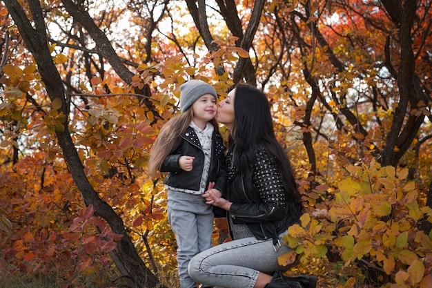 Szczęśliwa rodzina matka i córka dziecka bawią się i śmieją na jesiennym spacerze. relacje matki i dziecka. modna mama i córka w stylowym wyglądzie z tymi samymi skórzanymi kurtkami i swetrami