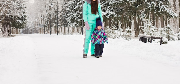 Szczęśliwa rodzina matka i córka dziewczynka grając i śmiejąc się w zimie na zewnątrz w śniegu.