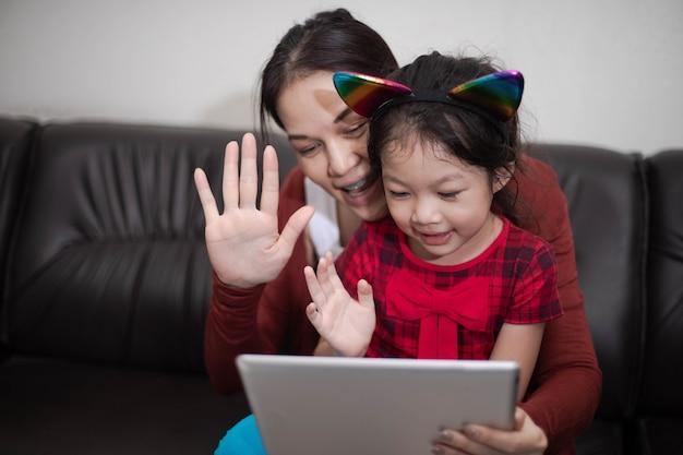 Szczęśliwa rodzina matka i córka za pomocą cyfrowego tabletu, siedząc na kanapie online studium w domu.