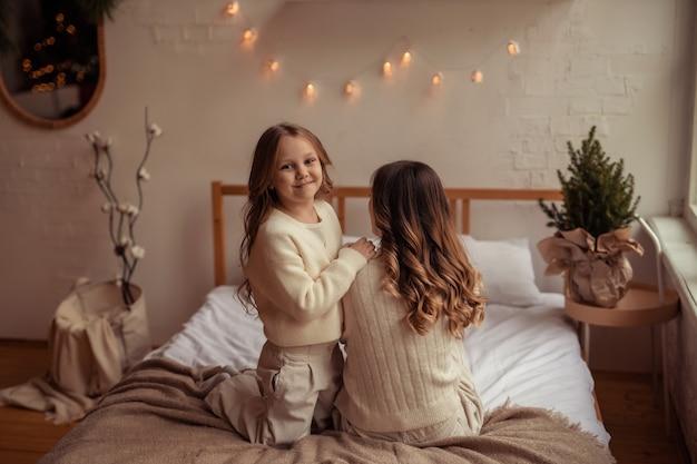 Szczęśliwa rodzina matka i córka zabawy w domu na łóżku