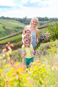 Szczęśliwa rodzina - matka i dwie córki z uśmiechniętymi twarzami na zewnątrz