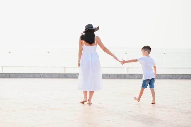 Szczęśliwa rodzina matka i syn na plaży nad morzem w lecie