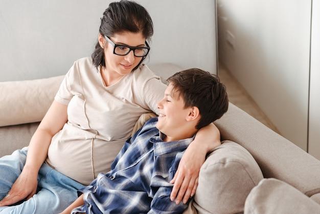 Szczęśliwa rodzina matka i syn, odpoczynek w salonie w mieszkaniu i razem siedząc na kanapie