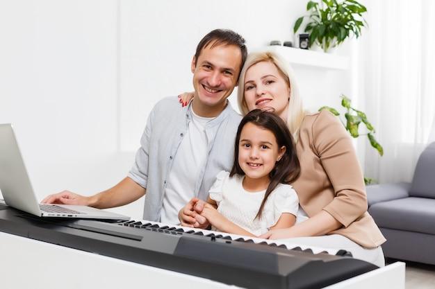 Szczęśliwa rodzina, matka, ojciec i córka grając na pianinie w domu, koncepcja relacji rodzinnych. szkoła muzyczna i rodzina muzyczna.