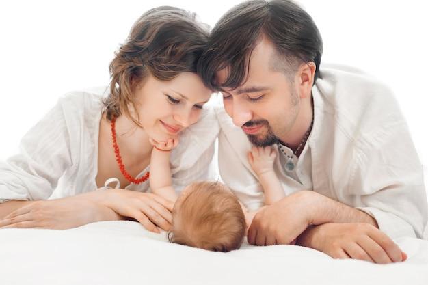 Szczęśliwa rodzina, matka, ojciec i córka odpoczywają na białym łóżku