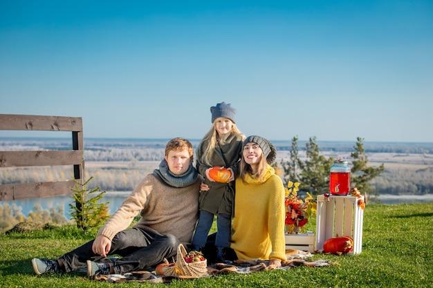 Szczęśliwa rodzina matka ojciec i córka razem w naturze na pikniku z dyniami w kratę