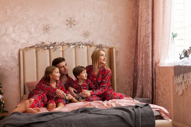 Szczęśliwa rodzina matka ojciec i dzieci w boże narodzenie rano w łóżku w piżamie