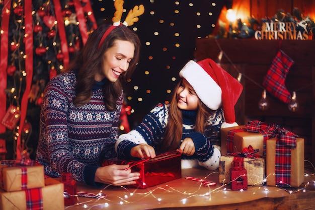 Szczęśliwa rodzina matki i dziecka pakuje prezenty świąteczne