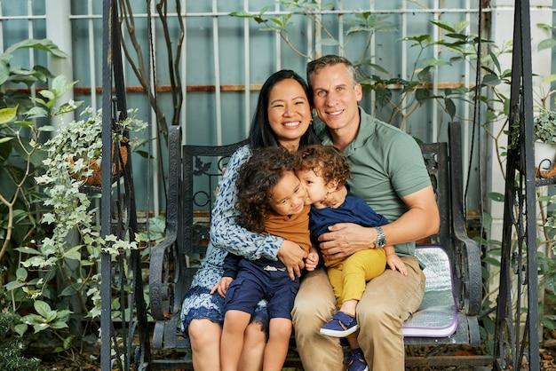 Szczęśliwa rodzina matki, ojca i dwóch małych synów siedzących na huśtawce na podwórku i uśmiechających się do kamery