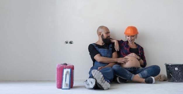 Szczęśliwa rodzina mężczyzna i kobieta w ciąży w kask męża i żony odpoczywają podczas dokonywania napraw w domu, siedząc przy ścianie i rozmawiając z brzuchem. koncepcja renowacji białej ściany i pokoju.