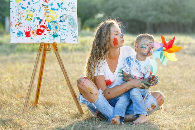 Szczęśliwa rodzina. młoda ładna matka zabawy z dziećmi na zewnątrz. malarstwo rodzinne