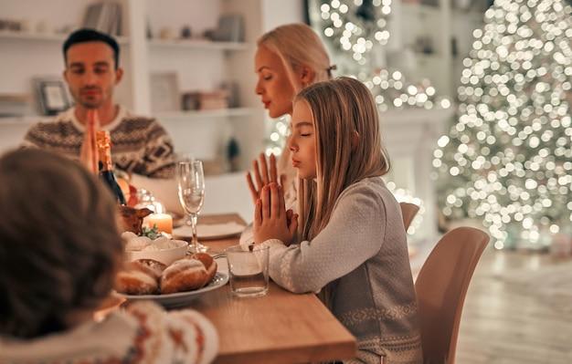 Szczęśliwa rodzina modląca się przy świątecznym stole