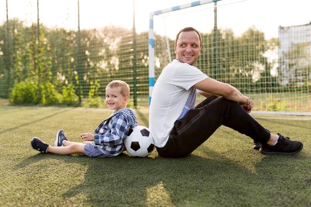 Szczęśliwa rodzina monoparental siedzi na trawie