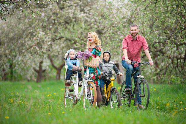 Szczęśliwa rodzina na bicyklach w wiośnie uprawia ogródek