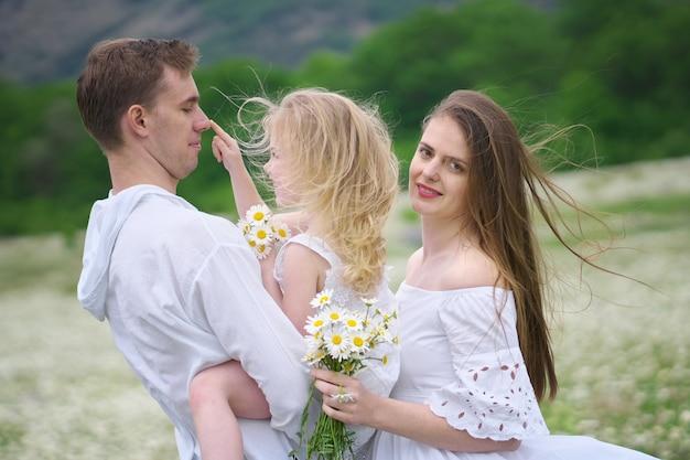 Szczęśliwa rodzina na dużej rumianku góry łące.