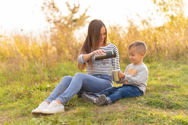 Szczęśliwa rodzina na jesienny spacer. młoda piękna matka z małym synkiem cieszy się naturę.