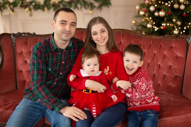Szczęśliwa rodzina na kanapie w pobliżu choinki. przytulna rodzinna atmosfera. cieszący się miłością przytulanie, święta ludzie