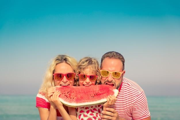 Szczęśliwa rodzina na letnie wakacje ludzie jedzący arbuza na plaży koncepcja zdrowego stylu życia