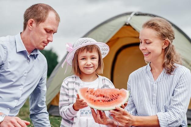 Szczęśliwa rodzina na pikniku na campingu. matka, ojciec i córka jedzenia arbuza w pobliżu namiotu na łące lub w parku