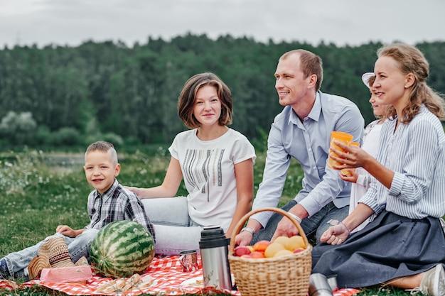 Szczęśliwa rodzina na pikniku. piknik na łące lub w parku. młodzi przyjaciele i ich dzieci w naturze