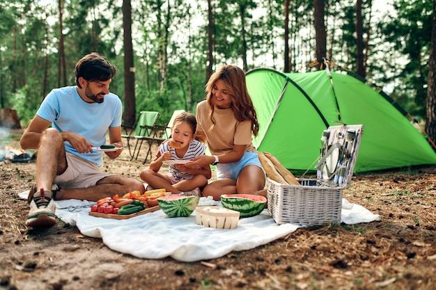 Szczęśliwa rodzina na pikniku siedzi na kocu w pobliżu namiotu w lesie na weekend. camping, rekreacja, turystyka.