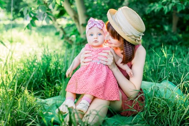 Szczęśliwa rodzina na pikniku w zielonym ogrodzie w słoneczny wiosenny dzień: piękna uśmiechnięta matka siedząca na zielonej trawie i jej mała roześmiana córka na nogach