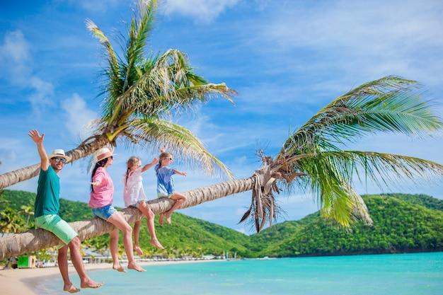 Szczęśliwa rodzina na plaży na palmie podczas letnich wakacji