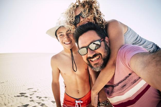 Szczęśliwa rodzina na świeżym powietrzu na plaży podczas wakacji turyści biorący selfie w szczęściu razem na wakacjach z kurortem wydm. radość z wolności i stylu życia z uśmiechem