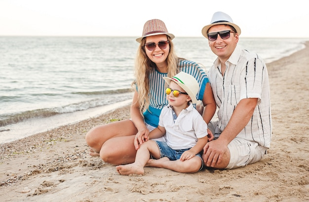 Szczęśliwa rodzina na wakacjach. na plaży siedzi mama, tata i mały syn. podróżująca rodzina. pocałunki, uśmiechy.