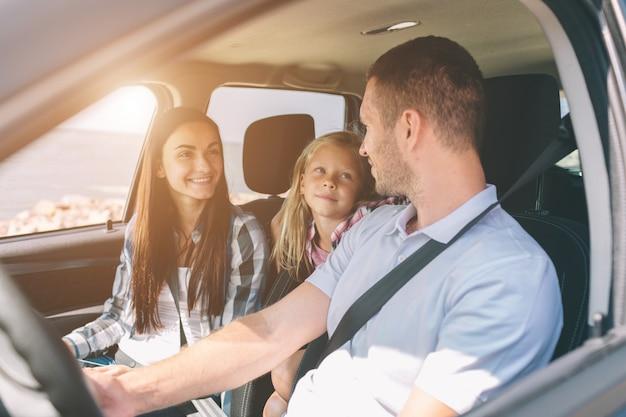 Szczęśliwa rodzina na wycieczce samochodowej w samochodzie. tata, mama i córka podróżują nad morzem, oceanem lub rzeką. letnia jazda samochodem