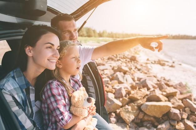 Szczęśliwa rodzina na wycieczkę samochodową w swoim samochodzie. tata, mama i córka podróżują nad morzem, oceanem lub rzeką. letnia jazda samochodem.